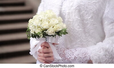 Beautiful bride holding wedding bouquet of flowers -...