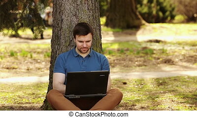 Man With Laptop Sitting On Ground Near The Tree
