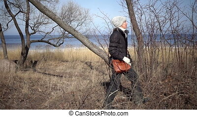 The young woman walks on the coast of the Gulf of Finland in...