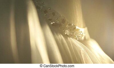 Beautiful stylish weeding dress with diamond belt close up lit by rays on sunset