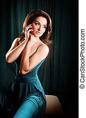 Beautiful Woman - A glamorous young woman sitting on a stool...
