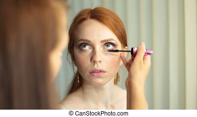 Make up artist at work, correcting eye lashes preparing...
