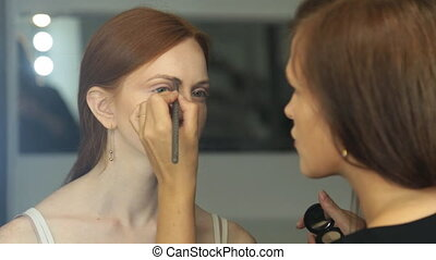 Makeup artist applying makeup to a model at a photo shoot