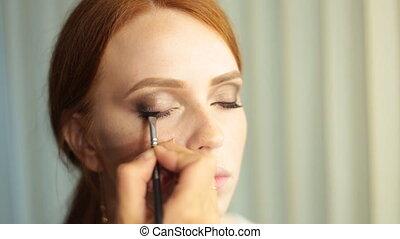 Make up artist at work, correcting eye lashes preparing...