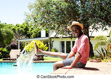 Smiling black man sitting by pool