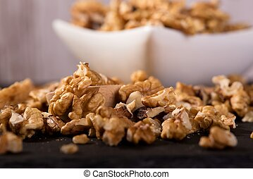 Spilled walnuts in front of square white bowl - Horizontal...