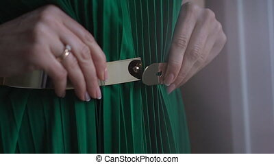 Woman unbuttons belt on her dress