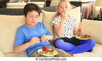 Cute girl and boy eating strawberry
