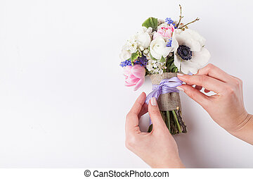 Florist making a beautifull spring bouquet - Two hands of...
