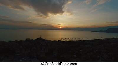 Wonderful panoramic view on sunset over beautiful lake Garda (Lago di Garda) with mountains, yachts and sailingboats in Bardolino harbor (Verona, Italy). Aerial view