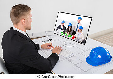 Architect Attending Video Conference In Office - Young Male...