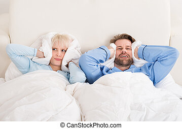 Couple Covering Ears While Sleeping On Bed - Young Unhappy...