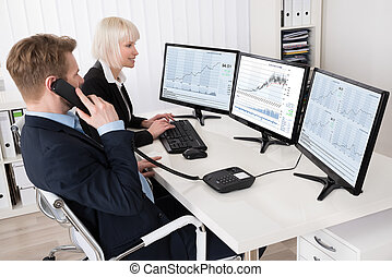 Two Businesspeople Analyzing Stock Charts