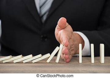 Businessman Hand Stopping Dominoes From Falling On Desk -...