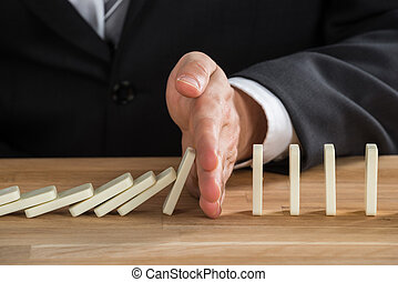 Businessman Stopping Dominoes From Falling - Close-up Of...