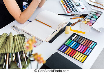 Female artist creating picture at workplace using gouache,...