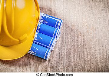 Wooden board with blue rolled up construction drawings...