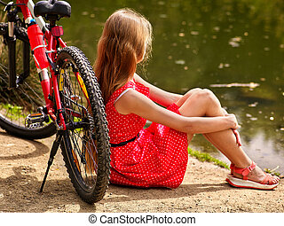 Bikes cycling girl into park Girl sits leaning on bicycle on...