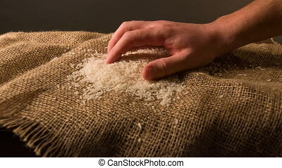 Person sifting rice on the sackcloth - Healthy grain. A...