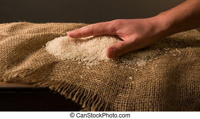 Person spilling rice on the sackcloth - best quality. A...