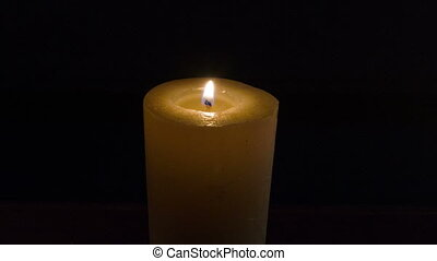 Wax candle burning on the black background