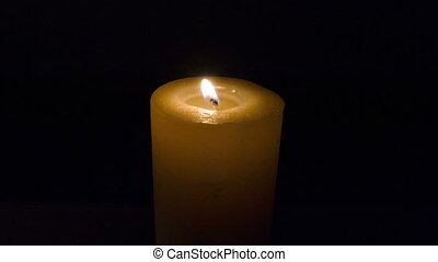 Candle burning on black background - Restless flame. Wax...