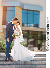 Young wedding couple kissing outdoors