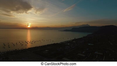 Aerial view on wonderful panoramic view on sunset over beautiful lake Garda (Lago di Garda) with mountains, yachts and sailingboats in Bardolino harbor (Verona, Italy).