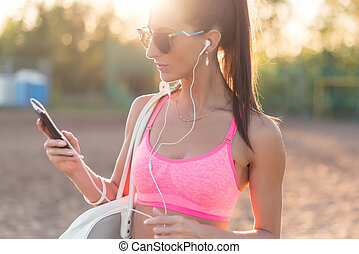 Athlete woman listening music looking at smartphone after...