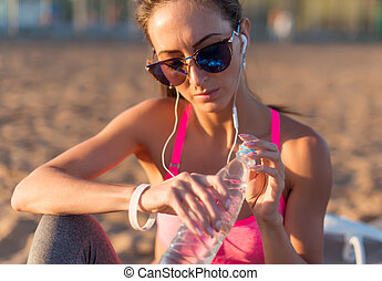 Beautiful fitness athlete woman drinking water - Beautiful...