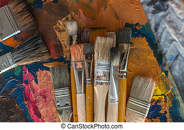 Paintbrush collection on old palette top view Mixing...