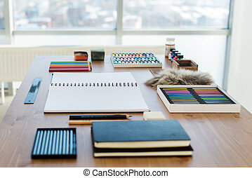 Side view of a painter workspace. Wooden desk with artistic...