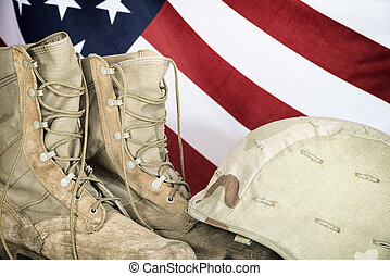 Old combat boots and helmet with American flag in the...