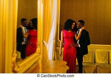 Sexy african women holds in hands her boyfriend's face. Luxury theatre interior background