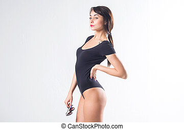 Young female model with perfect body and tail hairstyle standing sideways, putting her arm on hip, holding sunglasses, not isolated.