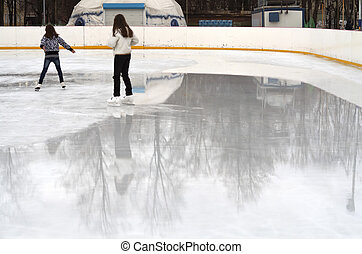 girls on the skating rink in spring - two girls skate on the...