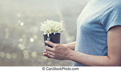Praying woman with white bouquet in hands to show respectt,...
