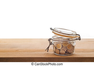 Tip box, coin in the glass jar on wooden white background