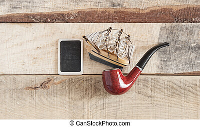 pipe and model classic boat on wood background