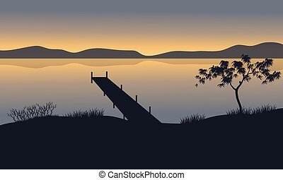 Silhouette of pier in lake