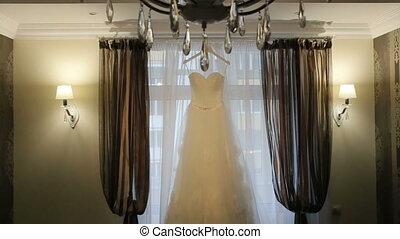 Beautiful white stylish wedding dress on hanger on the...