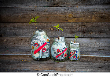 Glass jars with money (dollars) from which the tree sprout...