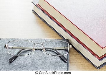 Glasses put on notebook on deck wood