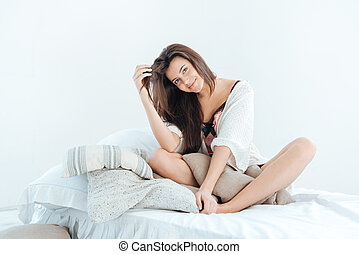 Happy attractive young woman smiling and sitting on bed