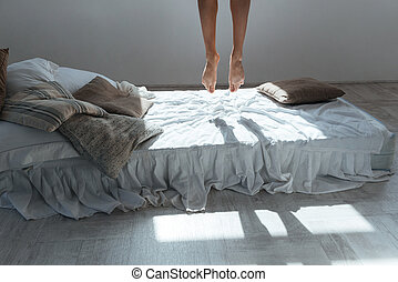 Slim legs of young woman flying in air above bed - Slim legs...