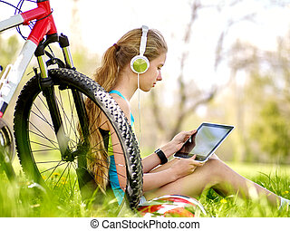 Bikes cycling girl wearing headset watch in pc tablet near...
