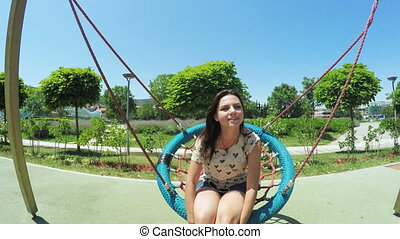 Girl is going to swing - On swing in park rides adult girl