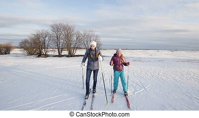 Cross-country skiing on field. - Two girls on cross-country...