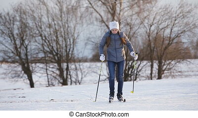 Cross-country skiing on field. - Girl on cross-country skis...
