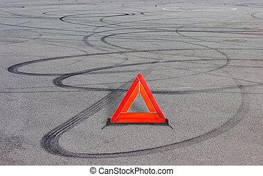 Warning triangle and tire tracks on asphalt